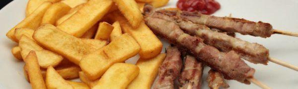 Arrosticini con cosce di tacchino servite con patatine fritte