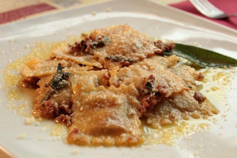 Ravioli di salsiccia e patate, menta, timo e erba cipollina conditi al piatto con burro, salvia e salsiccia sminuzzata